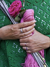 Christine Vermeersch holding pink yarn, vintage knitting needles, and a red rose